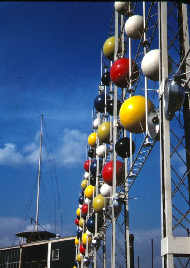A screen of yellow, red, white and navy  balls, reminiscent of an atomic model.