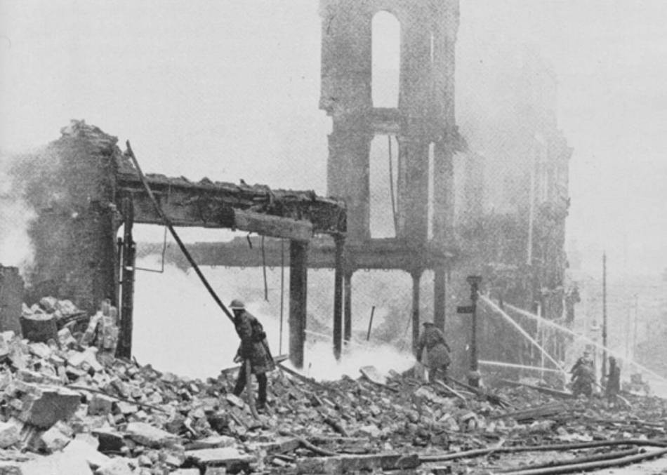 A firefighter puts out a fire in the ruins of a building.