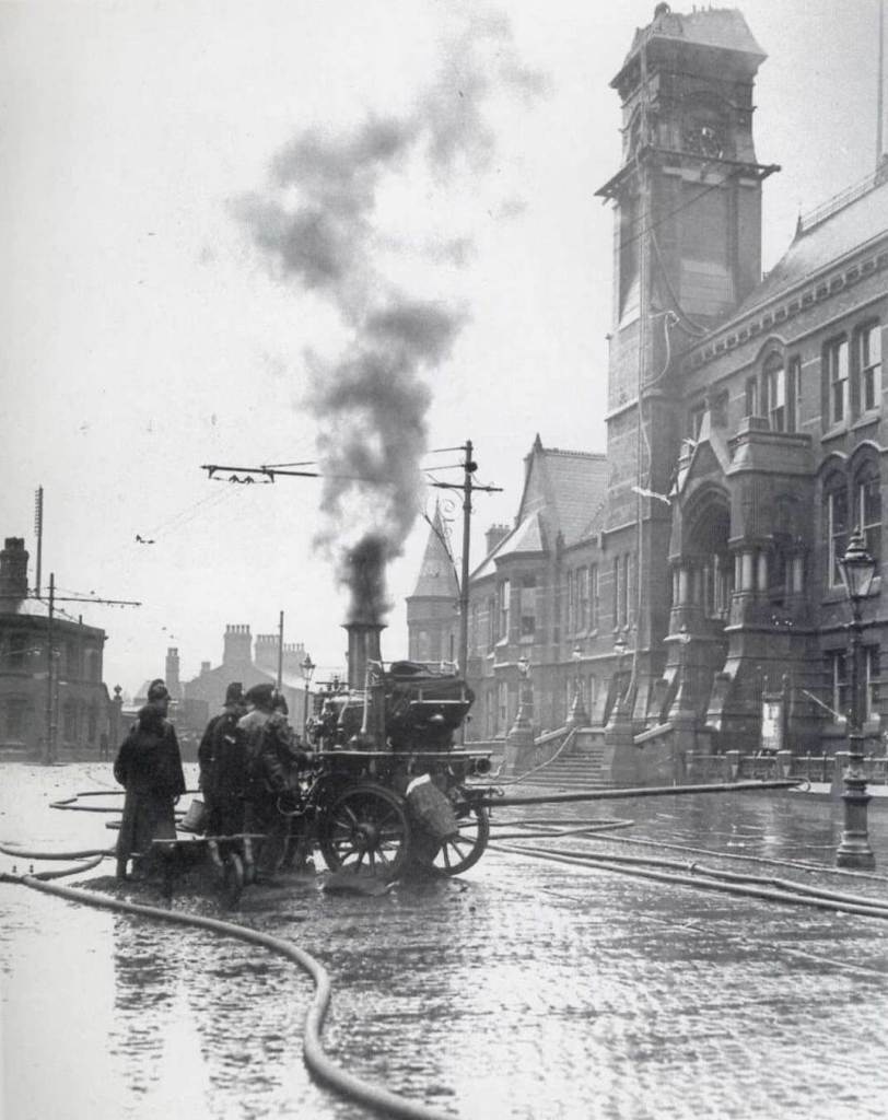 Firefighters with a steam pump infront of St Helen's Town Hall