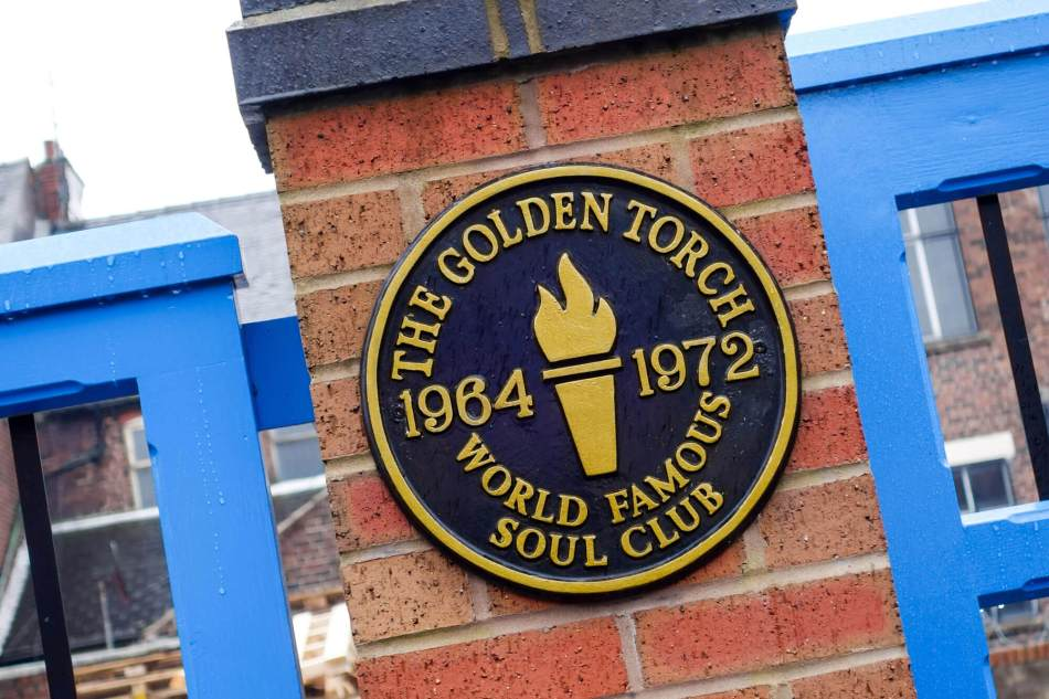 A plaque on a building at the site of a famous Northern Soul Club, the Golden Torch; the plaque includes the club's 'torch' badge.