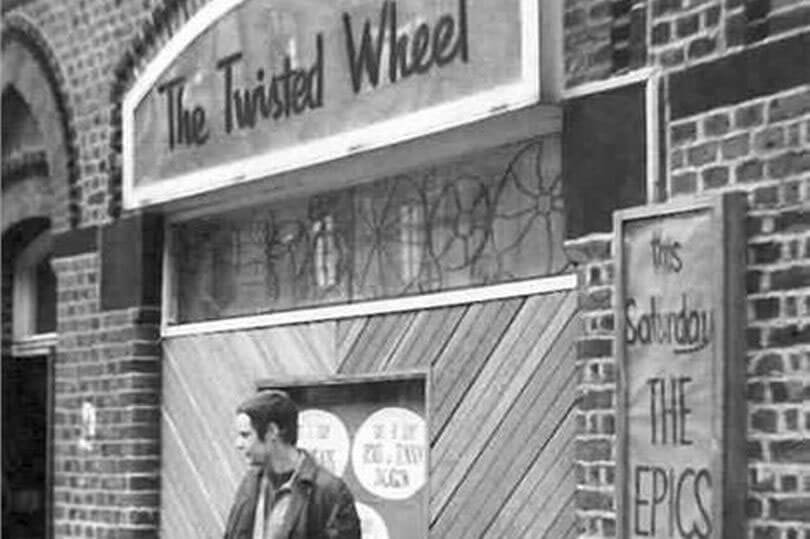 A man standing outside a club with a sign that reads 'The Twisted Wheel', the panel above the entrance is decorated with wheel motifs.