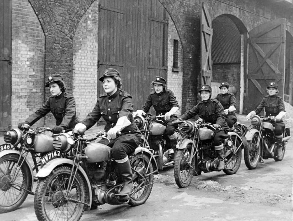 Six women in uniform ride motorbikes.
