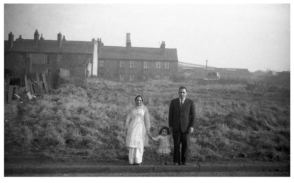 Smartly dressed man and woman hold the hand of a little girl between them, behind them is long grass and some small houses.