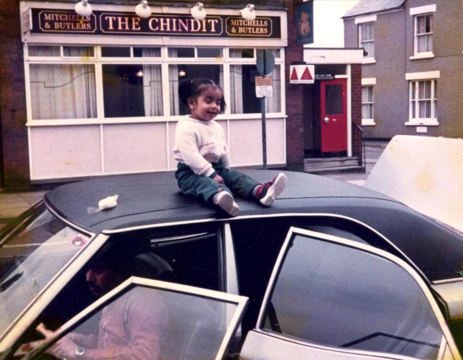 A small girl sits on the roof of a car outside a Desi pub