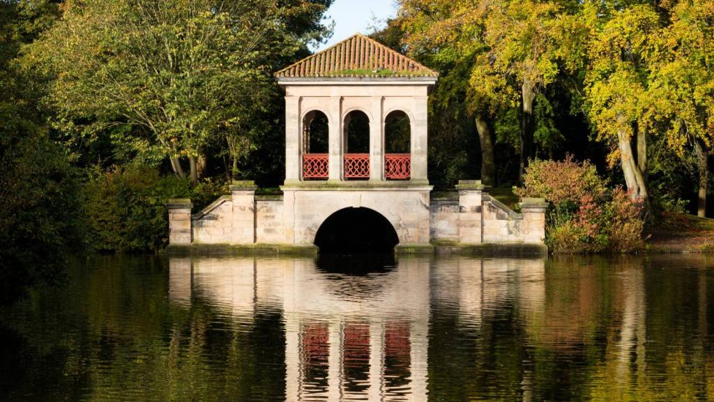 Boathouse structure in the middle of a pond surrounded by trees