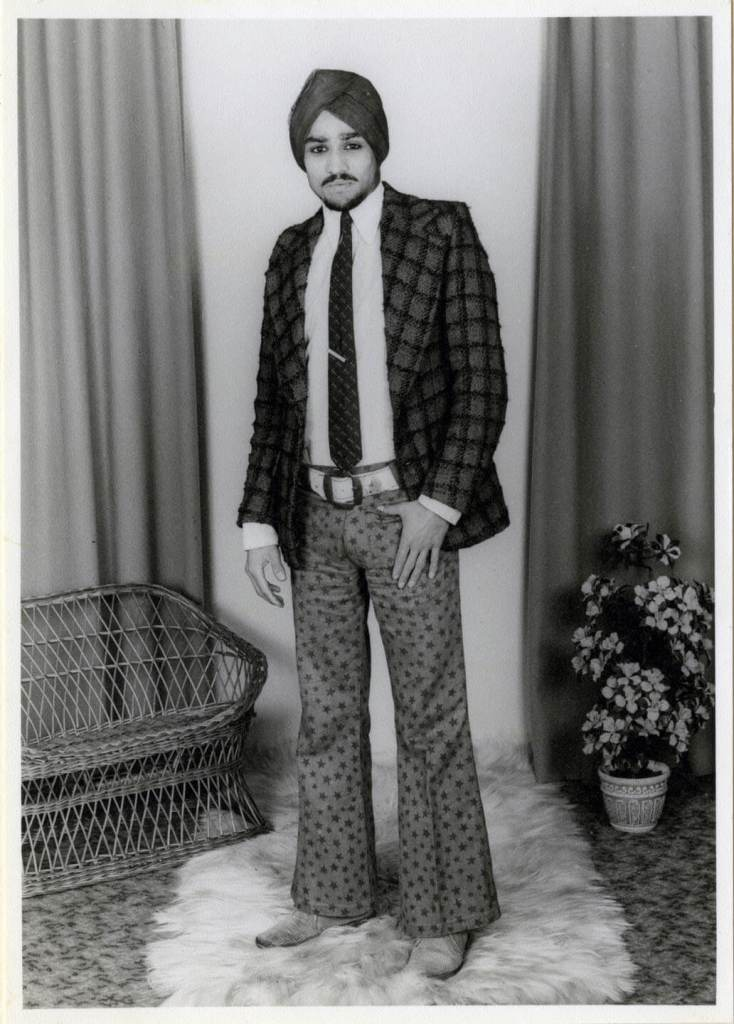 A young man wears a turban, blazer and tie, and some flares with stars on.