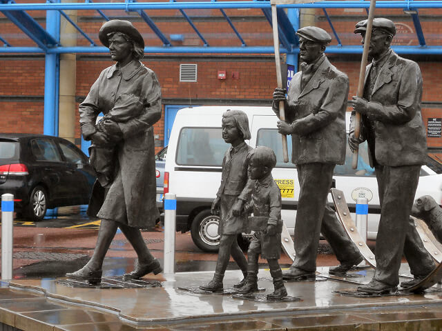 Bronze statue of the Jarrow marchers, featuring two men holding placards behind a woman holding a baby and two small children.