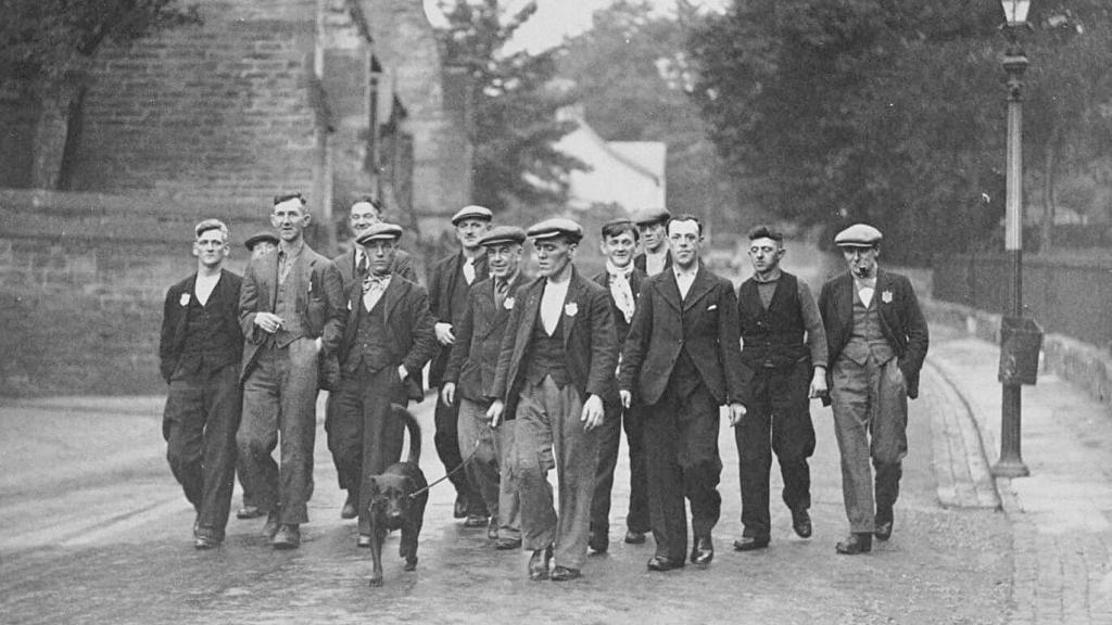 A group of 12 smartly dressed men walk down the street with the man at the front walking a dog.