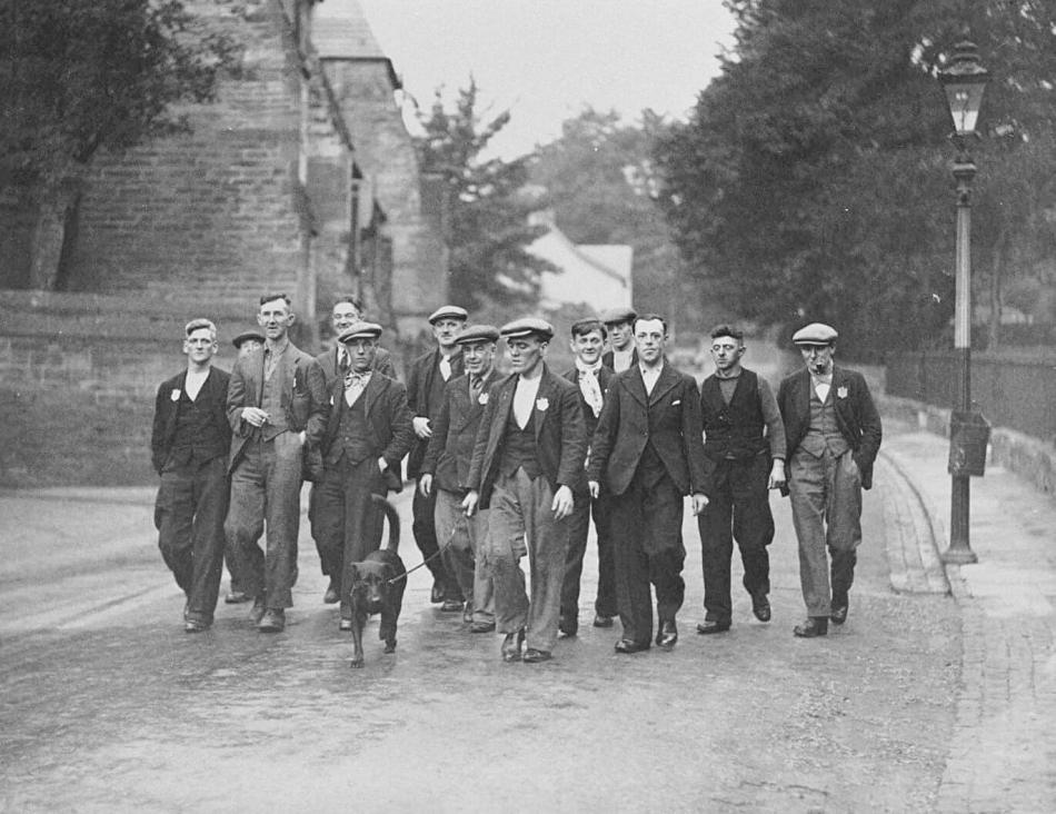 A group of smartly dressed men with flat caps march. One man at the front walks a dog.