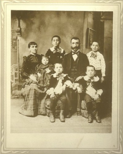 "From left: Gitel Frank Broida likely holding Theodore ""Dave"", Phillip standing in back, John/Zelig Broida, son Joseph standing on far right, Max sitting on right, son Morris sitting in front on left."