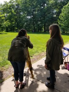 Students practicing total station measurements, with one student leaning over to use the station, another writing notes, and one in the distance holding a reflective prism