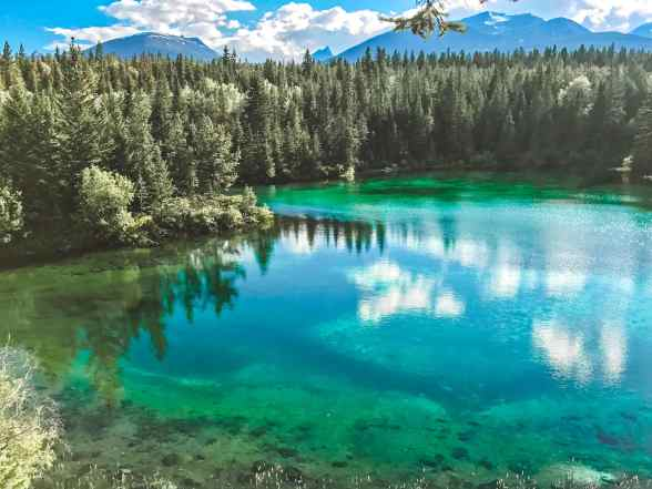 Fourth Lake in Jasper National Park, Alberta Canada and more incredible photos to inspire your Canada National Park Adventure. Covering Jasper + Banff + Yoho | HerLifeAdventures.Blog | #traveldestinations #travelideas #northamericatravel #traveltips  #travelhacks #travelguide #adventuretravel #roadtrip #nationalpark #nationalparkroadtrip #alberta #canada #britishcolombia