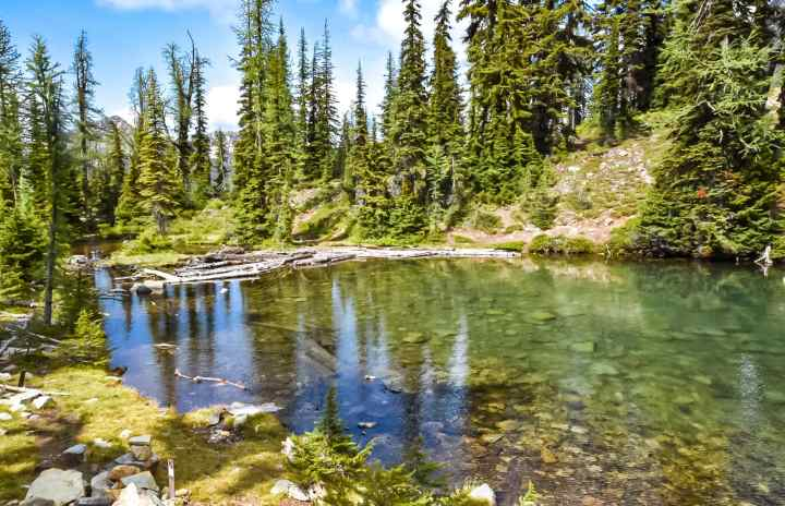 Blue lake hike in North Cascades looks like a rainbow reflection. North Cascades National Park ultimate guide. | HerLifeAventures.Blog | #traveldestinations #northcascadeshighway #northamericatravel #hiking #camping #usdestinations #travelhacks #travelguide #adventuretravel #roadtrip #nationalpark #nationalparkroadtrip #northcascades #washington