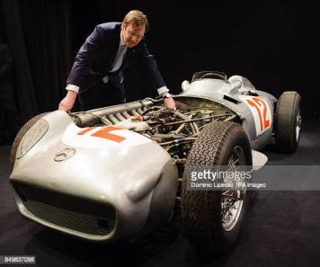 Chairman of Bonhams auction house Robert Brooks examines the 1954 2.5 litre Mercedes-Benz W196 Formula 1 Grand-Prix single-seater driven by Juan Manuel Fangio, at a photocall at Bonhams, in central London. (Photo by Dominic Lipinski/PA Images via Getty Images)
