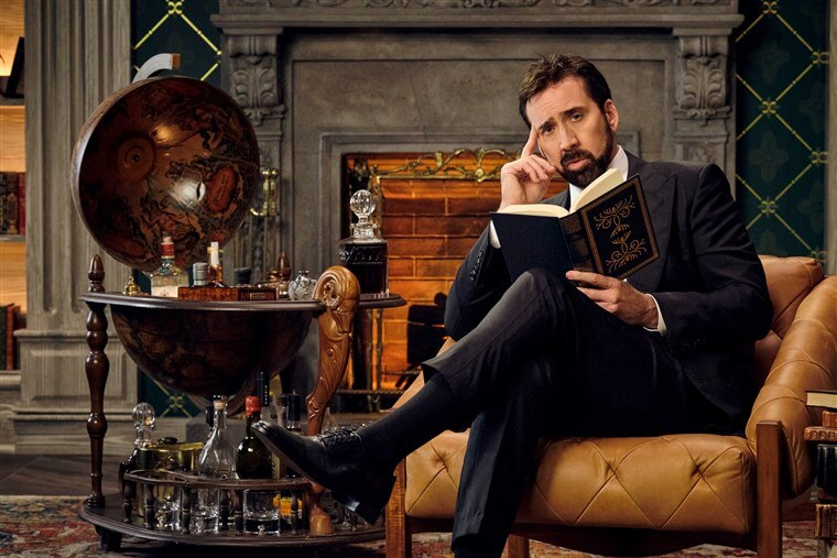 Nicholas Cage sitting in an armchair with a book; a chimney and globe-like bar in the background