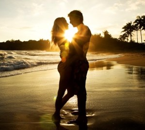 A couple embracing on a beach at sunset.