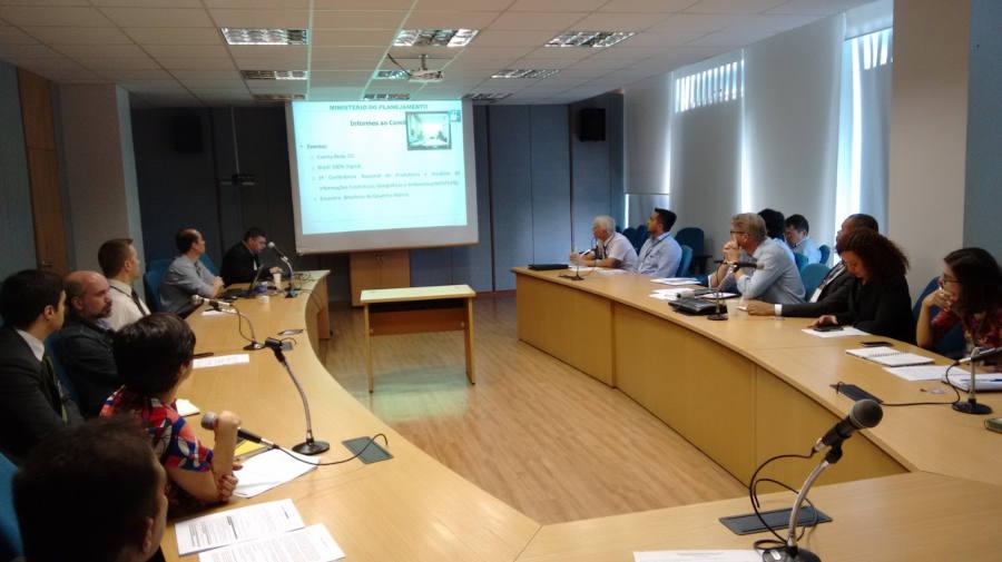 Representantes do comitê reunidos em volta de uma mesa assistem a uma apresentação