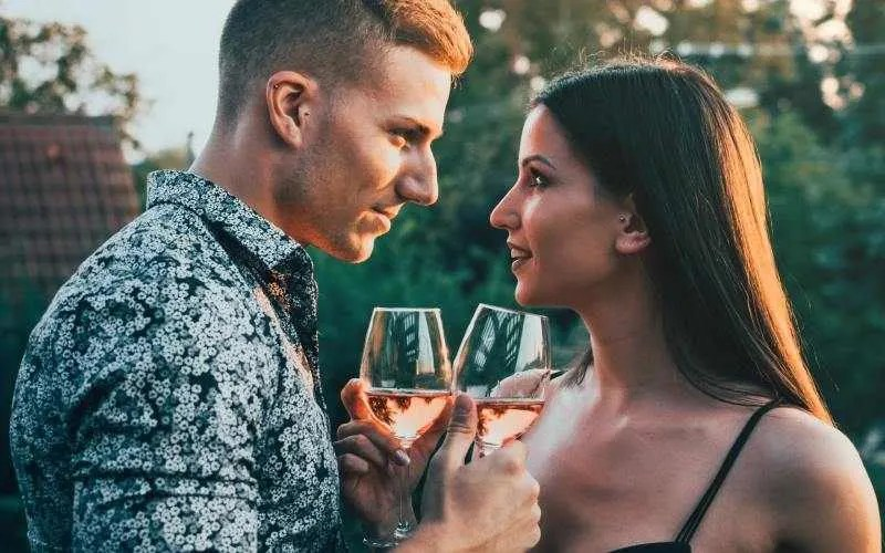 Sensual man and woman facing each other very close with wine glasses in their hands