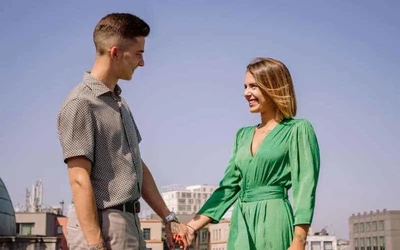 Woman in green dress holding hands with young man