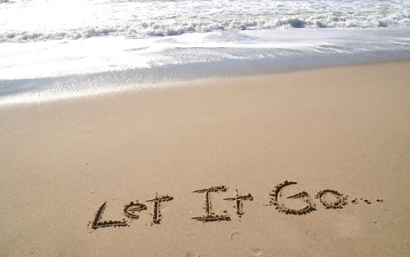 Let it go written on the beach sand during daytime