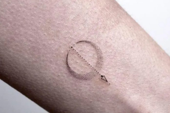 small arrow circled by a moon tattoo on the wrist
