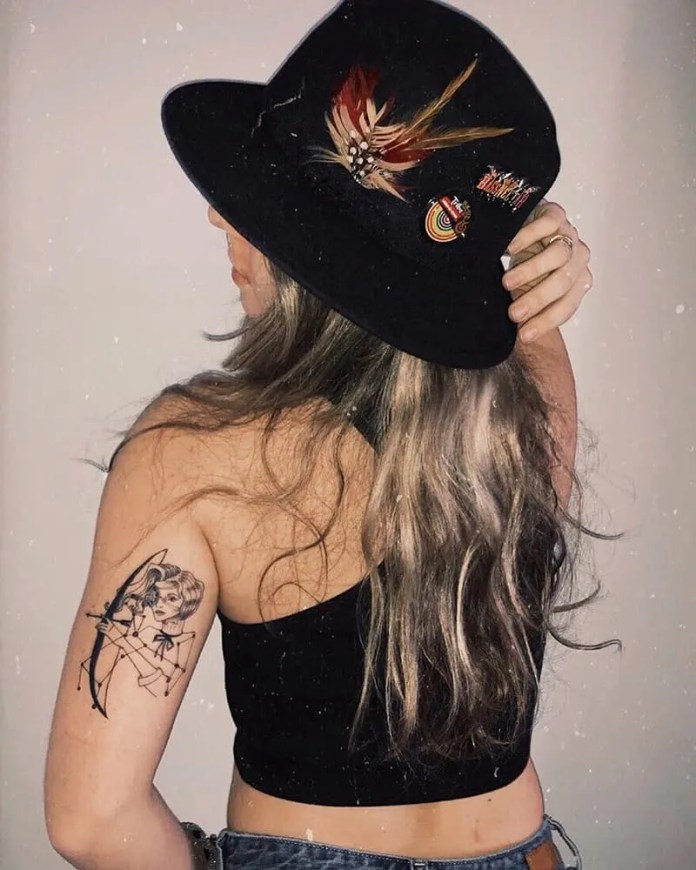 woman shooting an arrow tattoo on back of the arm