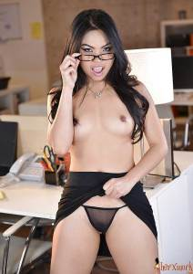 Sexy secretary holding her glasses and showing her natural tits and panties in the office.
