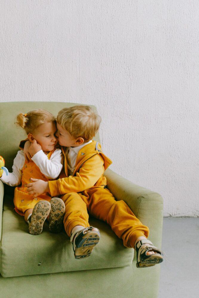 Het Gezinsleven - Moeder en Kind - Kind 4 - 12 jaar - Kleuterverliefdheid - Een jonge kleuter geeft een vriendinnetje een kusje op de wang