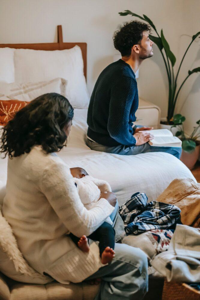 Het Gezinsleven - Lifestyle - Mannen - Top 10: zwangerschapsboeken voor mannen - Vader is druk een boek aan het lezen terwijl zijn vrouw voor de baby zorgt.