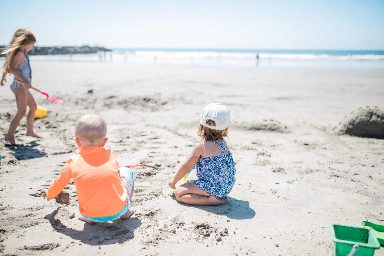 Het Gezinsleven - Moeder en Kind - Moeders - Zonbescherming voor kinderen - Kinderen spelen op het strand