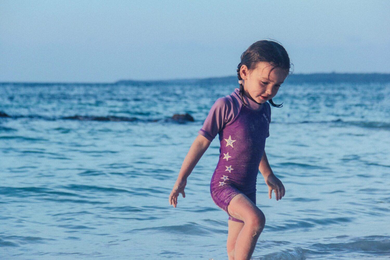 Het Gezinsleven - Moeder en Kind - Moeders - Zonbescherming voor kinderen - Meisje speelt in UV-werende kleding in de zee