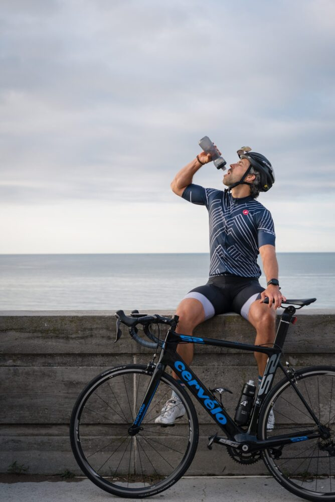 Het Gezinsleven - Lifestyle - Sporten - Drinken en eten voor het sporten, hoe zit het? - Man drinkt tijdens zijn fietstocht