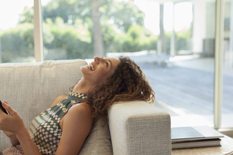 Het Gezinsleven - Lifestyle - Mindset - Lachen is gezond! - Lachende vrouw op de bank