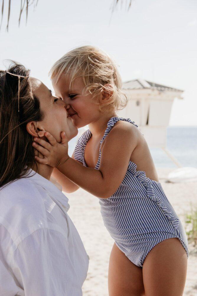 Het Gezinsleven - Lifestyle - Hobby's - Boeken - 10 nieuwe romans voor de zomer van 2021! - Dochter geeft mama een kusje op het strand