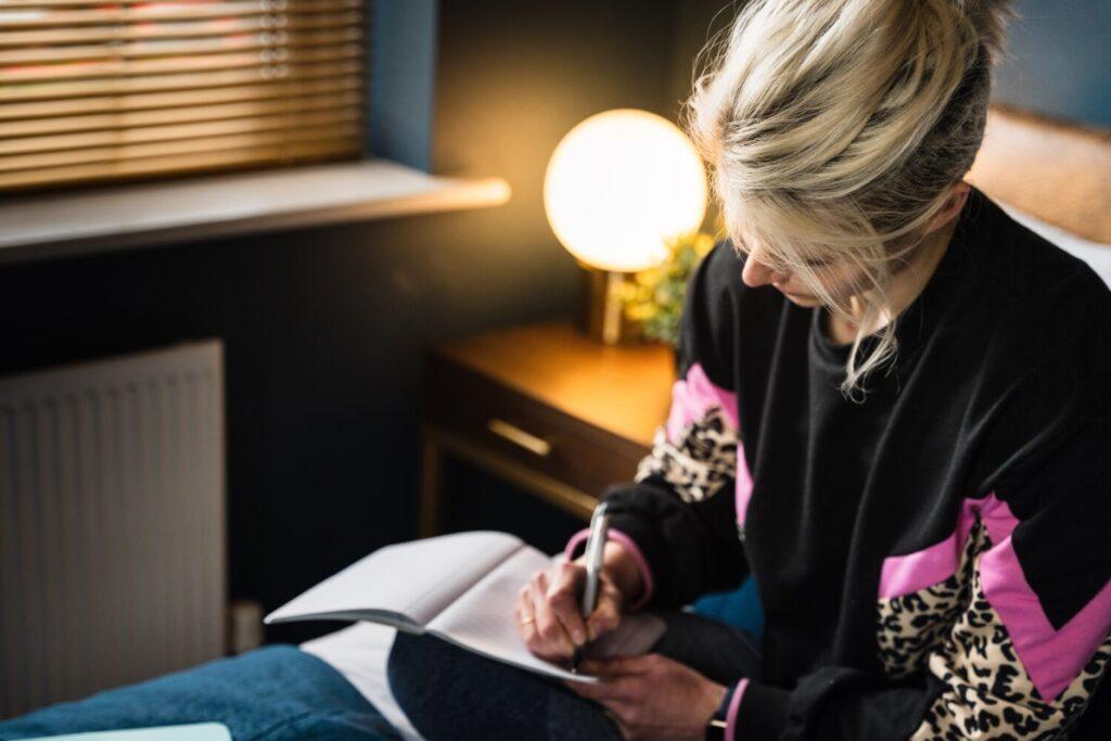 Het Gezinsleven - Lifestyle - Mindset - Piekeren in de nacht - Vrouw schrijft van zich af in bed