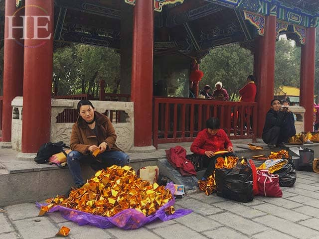 visitors fold gold fortune papers at a park in zhengzhou china