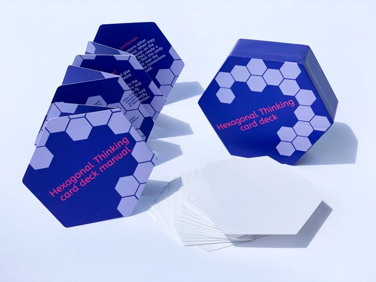 Hexagonal thinking card deck with box and instruction manual on white background