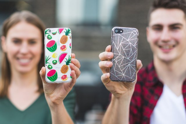 A boy and a girl showing their iPhones cases