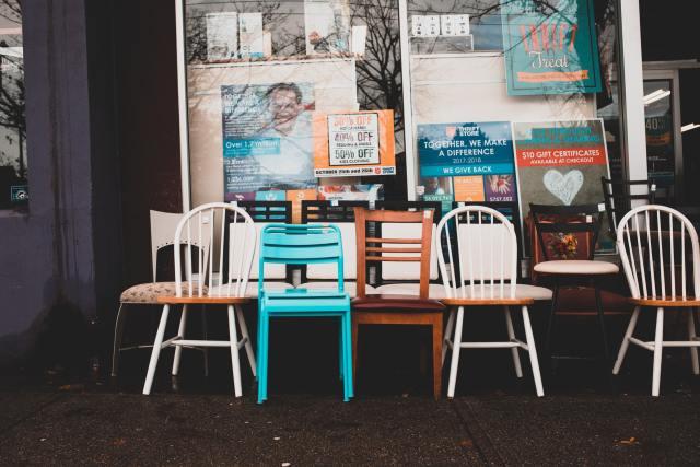 Várias cadeiras em segunda mão à frente de uma loja