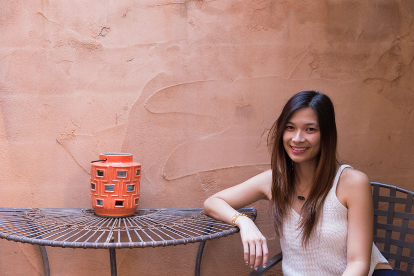 Sitting in a courtyard with my arm resting on a table and an orange lantern on the table