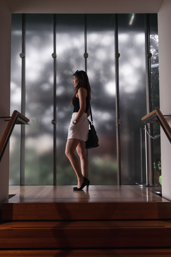 Me standing near a window, atop a small set of stairs, facing to the side