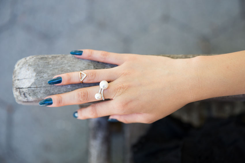 My hand with dark teal painted fingernails, wearing a pearl ring and a gold midi ring