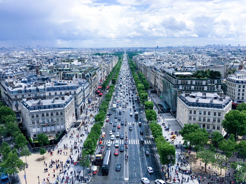 Street view of lots of cars and traffic, taken from the top of the Arc de Triomphe