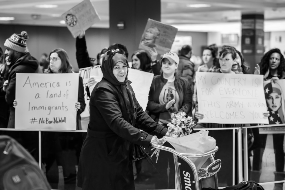 """A headscarf-wearing woman pushes a luggage trolley at Dulles International Airport in Virginia amidst protesters holding signs that read """"America is a land of Immigrants #NoBanNoWall"""" and """"My country is for everyone -- This Army veteran welcomes you"""""""