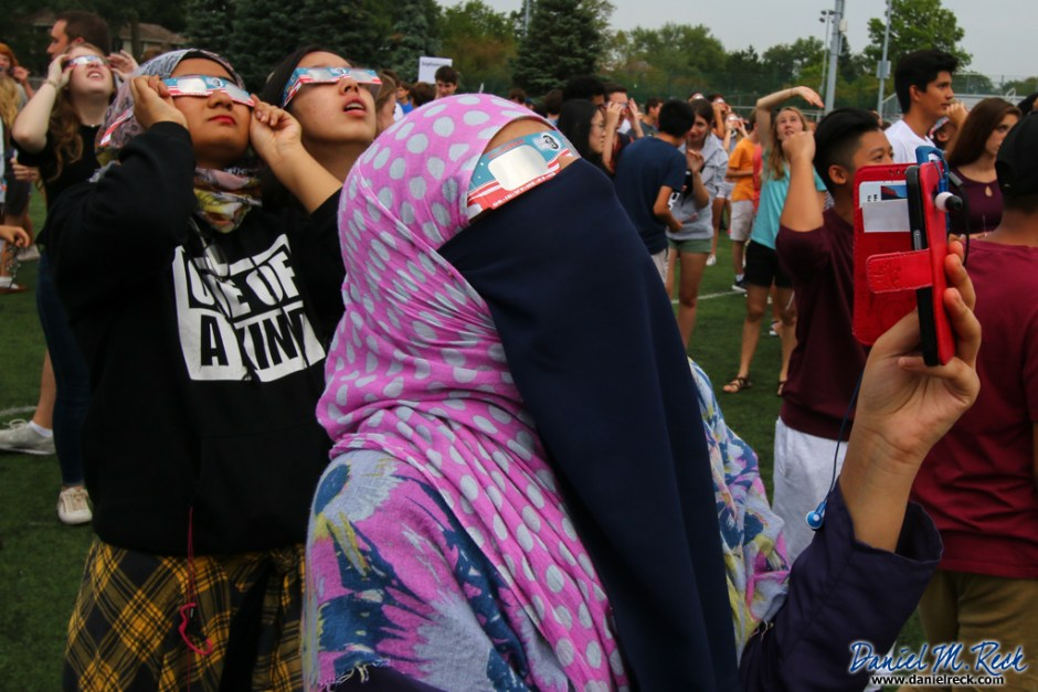 Headscarf-wearing girls in the foreground stare at a solar eclipse in an overcast sky through American flag framed protective cardboard glasses, amidst clusters of students and teachers in Illinois.