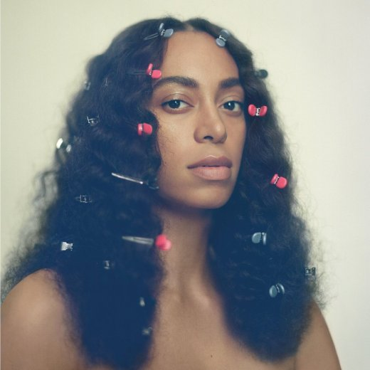 "Image: ""A Seat at the Table"" album cover, Solange Knowles from the shoulders up with alternating pink and light blue clips in her hair"