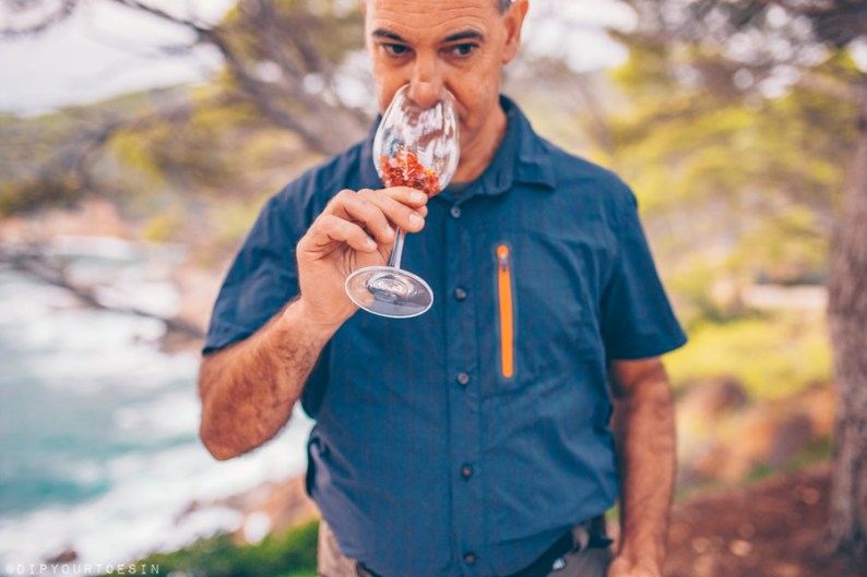 Evarist March from NaturalWalks smelling wildflowers in a wine glass | Costa Brava's Coastline