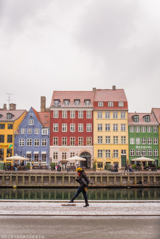 Eulanda walking along Nyhavn with colourful houses in background | Explore Copenhagen