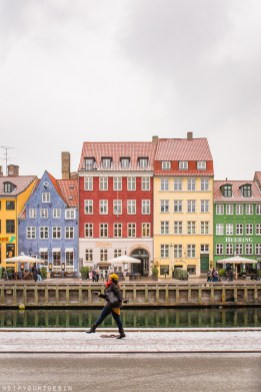 Eulanda walking along Nyhavn with colourful houses in background | Visit Copenhagen