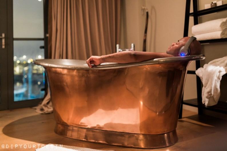 Man in copper bathtub in Salthouse Harbour Hotel, Ipswich, a luxury boutique hotel in Suffolk